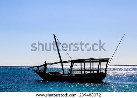 Traditional fisherman boat lying near the beach with blue sky - stock photo