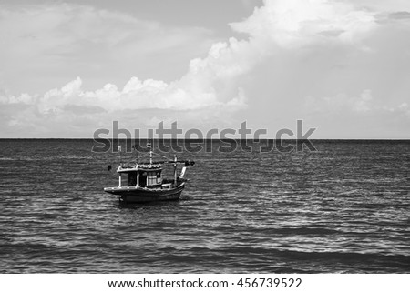 traditional fishing boat laying alone on the sea,black and white high contrast color picture style,selective focus