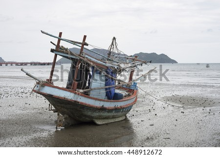 traditional fishing boat laying on a beach near the sea with mountain and island, selective focus,filtered image