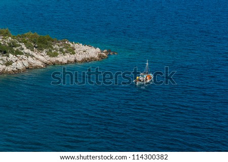 Traditional fishing boat near a promontory in Greece