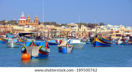 traditional fishing boats in the harbour of Marsaxlokk , Malta  - stock photo