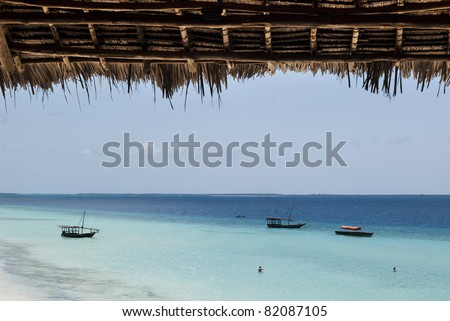 Traditional fishing wooden dhows moored off the coast of Zanzibar, Tanzania. - stock photo