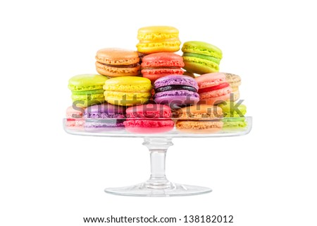 traditional french colorful macarons in a glass cake stand on white background