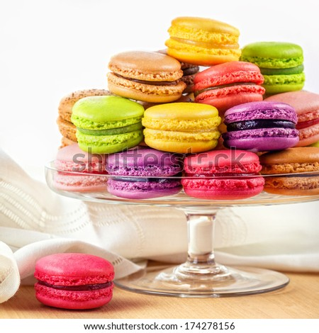 traditional french colorful macarons in a glass cake stand on wooden table - stock photo
