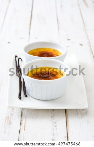 Traditional French creme brulee dessert with caramelized sugar on top, on white wooden table