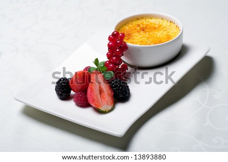 Traditional french cuisine - originally decorated creme brulee with fresh berries - stock photo