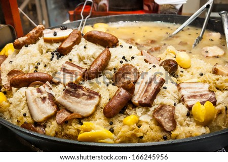 Traditional french dish at Christmas market in Paris - Sauerkraut  cooked in Riesling wine with sausages, meats and potatoes.  - stock photo