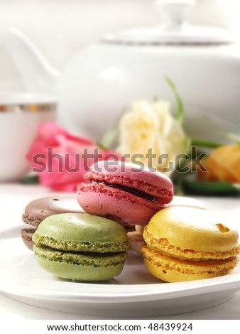 traditional french macarons with tea set on the background - stock photo