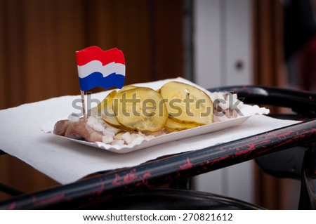 Traditional Fresh Salted Herring Covered with Onions and Bittersweet Cucumbers with a Decorational Dutch Flag - stock photo
