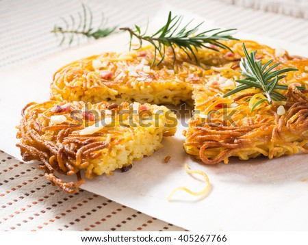 Traditional fried spaghetti pizza of Southern Italy with salami and cheese decorated with rosemary sprigs - stock photo