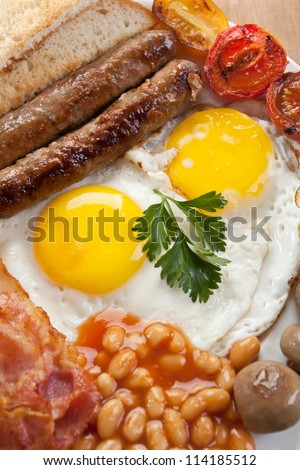 Traditional Full English Breakfast -fried sunny-side-up eggs, sausages, beans, mushrooms and bacon - stock photo