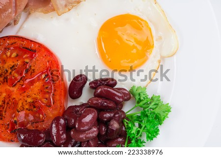 Traditional Full English Breakfast with fried eggs sausages beans mushrooms and bacon as haute cuisine  - stock photo