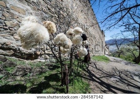 Traditional Georgian fur hats made of sheep wool in front of Medieval Ananuri Castle over Aragvi River in Georgia - stock photo