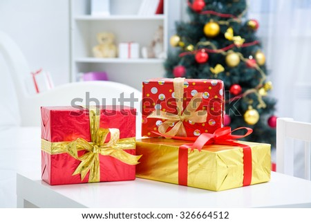 Traditional gifts and  Christmas tree with baubles and gifts in room - stock photo