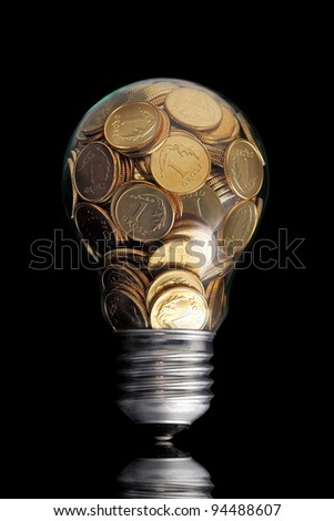 Traditional glass bulb with many golden coins on black - stock photo
