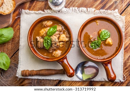 Traditional goulash soup with pork and dumplings. - stock photo