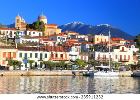 Traditional Greek harbor and town and distant mountains, Greece - stock photo