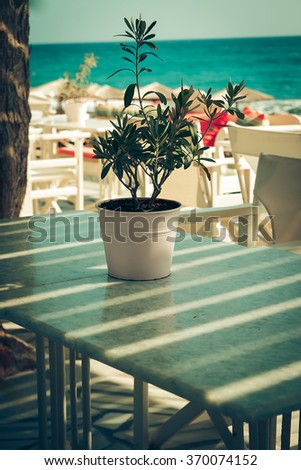 traditional greek outdoor restaurant on terrace overlooking Mediterranean sea (Greece ). empty table at an street sea restaurant. toned image. - stock photo