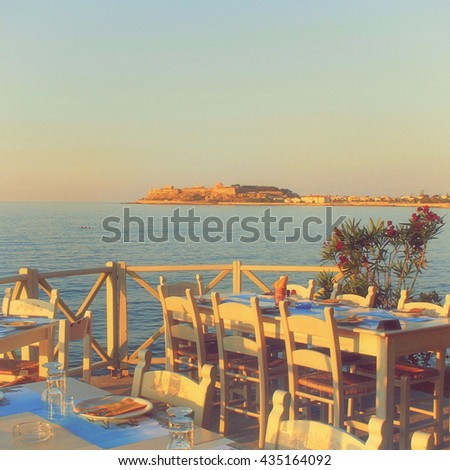 traditional greek outdoor restaurant on terrace with sea view at street village restaurant, Crete, Greece. Sunset light. Vintage film effect, square image - stock photo