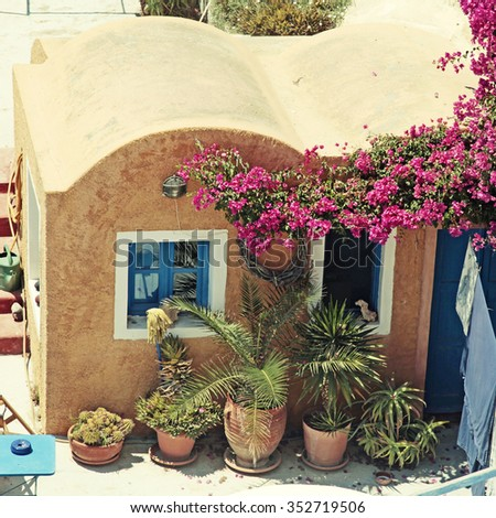 traditional greek red building with patio and flowers of Oia village, Santorini island, Greece. Square toned image - stock photo