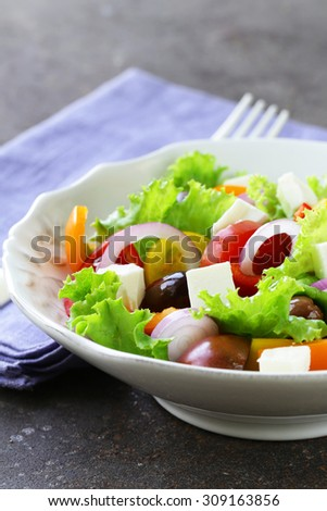 Traditional Greek salad with feta cheese, tomatoes, olives and green lettuce - stock photo