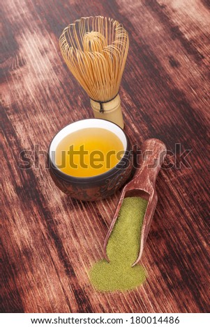 Traditional green powdered tea matcha with cup of tea, bamboo chasen on wooden background. Healthy tea drinking. - stock photo