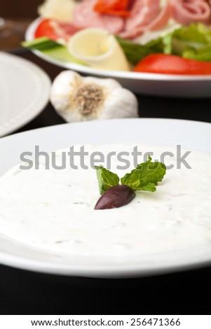 Traditional Gyro sandwich tzatziki sauce garnished with a kalamata olive and mint. Shallow depth of field. - stock photo