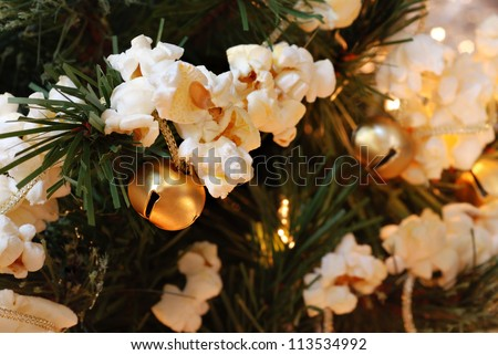 Traditional handcrafted popcorn garland (strung together with golden jingle bells) on artificial christmas tree with lights.  Macro with shallow dof. - stock photo