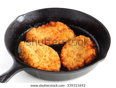 Traditional Hanukkah potato latkes frying in cast iron pan - stock photo