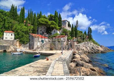 Traditional harbor surrounded by stone pier near the Adriatic sea, Trsteno, Croatia - stock photo