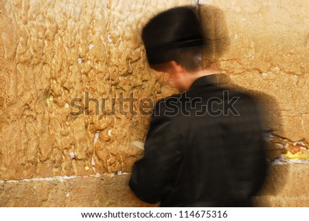 Traditional Hassidic Man Praying at the Western Wall moving as a candle in the wind. - stock photo