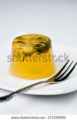 traditional homemade chrysanthemum tea herbal jelly on square white plate with fork against white background - stock photo
