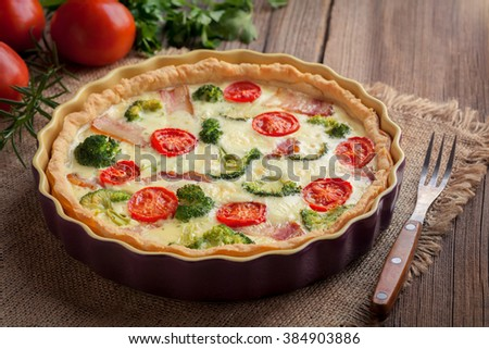 Traditional homemade quiche lorraine tart pie with broccoli, bacon, cheese and tomatoes in baking dish on vintage cloth. Wooden table background and rustic style.