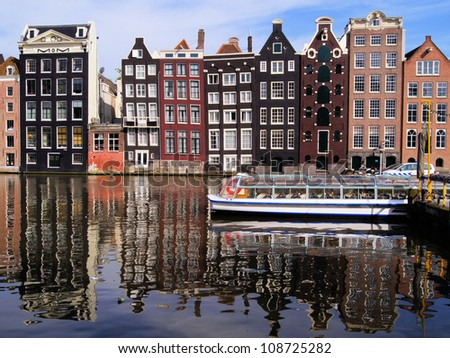 Traditional houses of Amsterdam with canal reflections, The Netherlands - stock photo