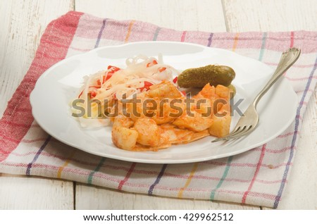 traditional hungarian meal, potato and pasta with paprika powder and sour gherkin on a white plate