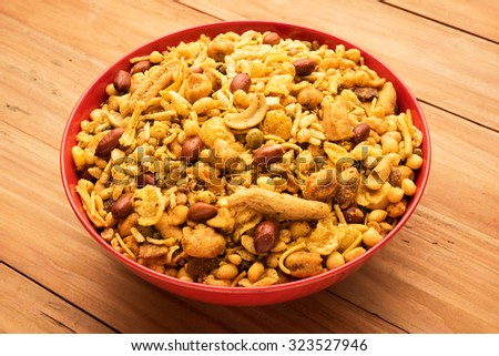 Traditional indian deep fried salty dish - chivda or mixture or farsan or farsaan made of gram flour and mixed with dry fruits in red bowl over wooden background. front angle and closeup, isolated - stock photo
