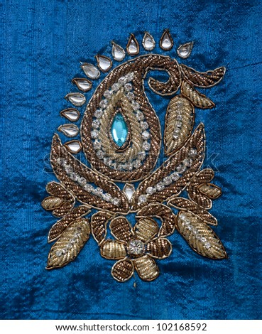 Traditional Indian embroidery detail on blue silk - stock photo