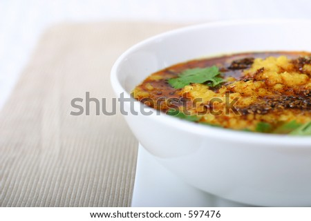 Traditional Indian lentil dish. Stir fried lentils, garnished with cumin and mint leaves. Shallow DOF. - stock photo