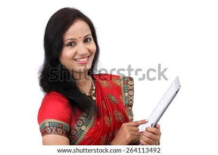 Traditional Indian woman using a tablet computer - stock photo