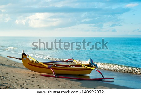 Traditional indonesian fishing boat on Bali ocean beach at sunrise - stock photo
