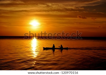Traditional indonesian fishing boat sailing through the sunset