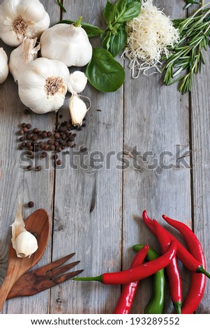 Traditional ingredients of italic cuisine - garlic, peppers, basil, rosemary and grained parmigiano. Copy space background. - stock photo
