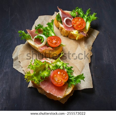 Traditional Italian antipasti crostini with ham, salad and tomato. Selective focus - stock photo