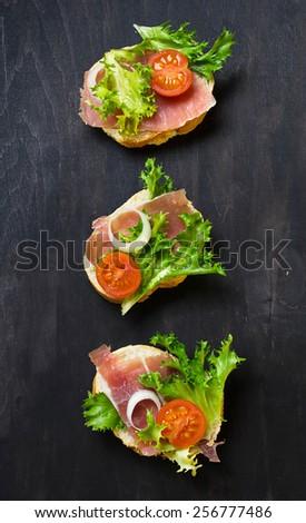 Traditional Italian antipasti crostini with ham, salad and tomato. Top view.  - stock photo