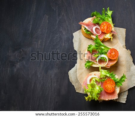 Traditional Italian antipasti crostini with ham, salad and tomato. Top view. Selective focus. Space for text - stock photo