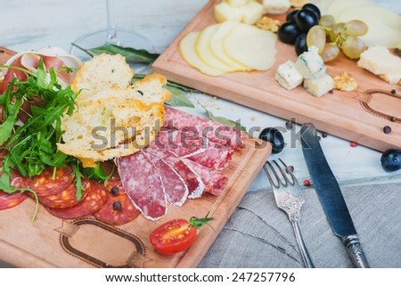 Traditional italian antipasto with prosciutto and different sorts sausage on a wooden table - stock photo