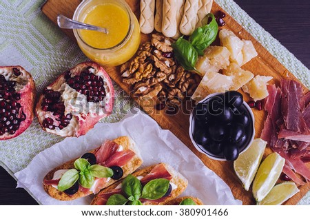 Traditional italian antipasto with prosciutto, cheese, olive and bruschetta. Appetizer set. Meat, vegetables and cheese on wooden board. Top view