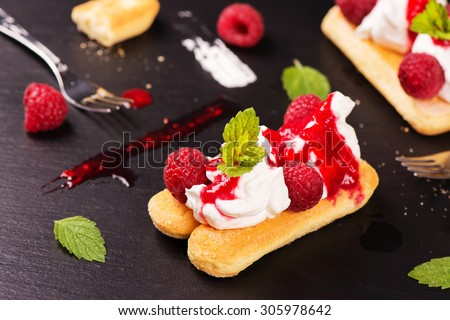 Traditional italian dessert - tiramisu cakes with raspberry and mint on black stone background. Selective focus - stock photo