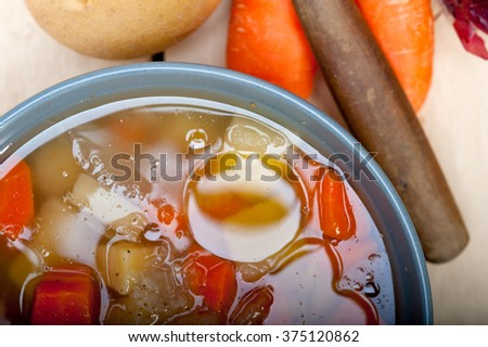 Traditional Italian minestrone soup on a rustic table with ingredients - stock photo