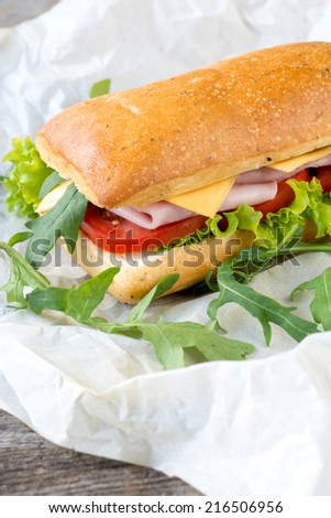 Traditional Italian panini sandwich in paper,selective focus - stock photo